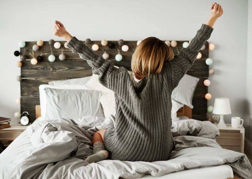 Woman in grey jumper stretching on wooden double bed with fairy lights on headboard