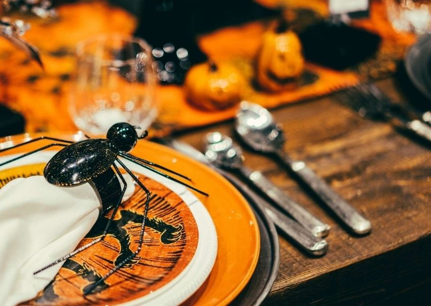 Halloween table decorations on wooden table with orange plates and large plastic spider