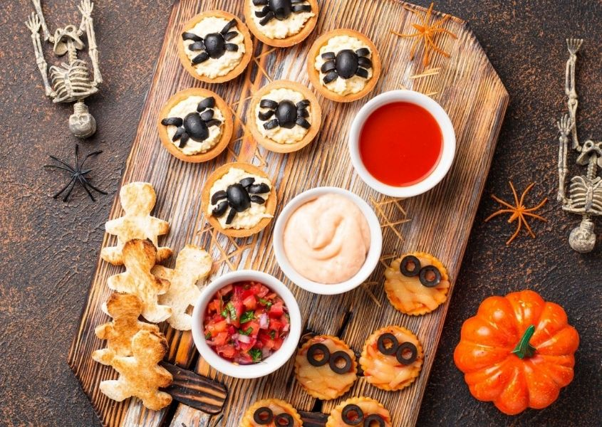 Platter of Halloween themed foods, including spider cupcakes and pumpkin biscuits