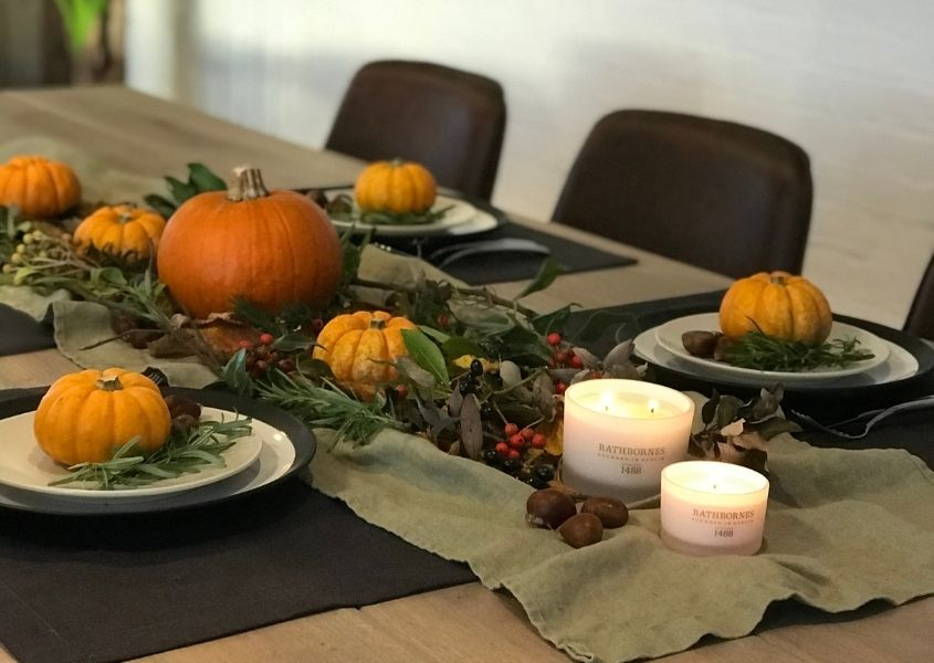 Wooden table decorated in Halloween theme with small pumpkins on plates and in middle of the table