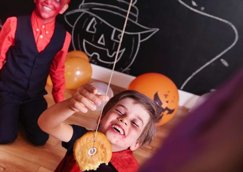 Two kids in Halloween costumes playing eat donut on string game