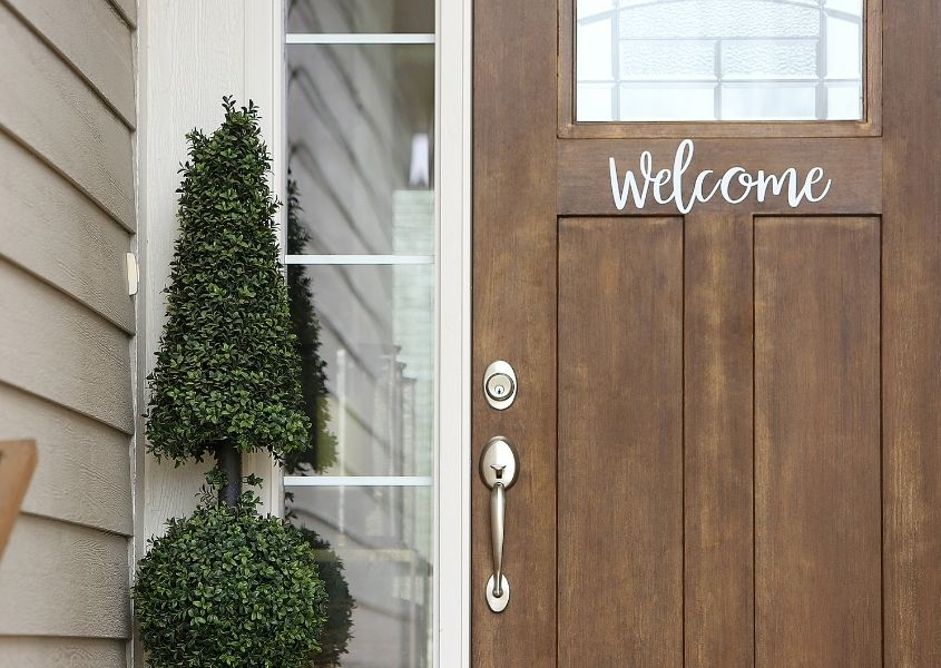 Natural wooden front door with words welcome on front with green topiary at entrance