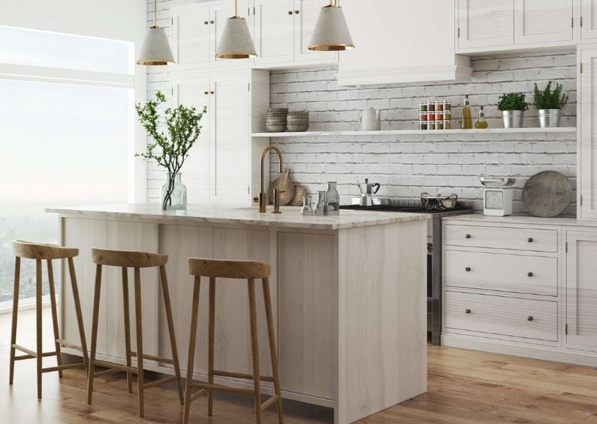 White kitchen with kitchen breakfast bar and three wooden bar stools and hanging pendant lights