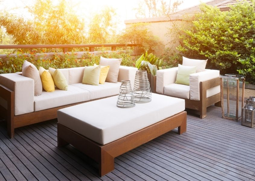 Outdoor sofa with white cushions and matching armchair and coffee table on wooden deck