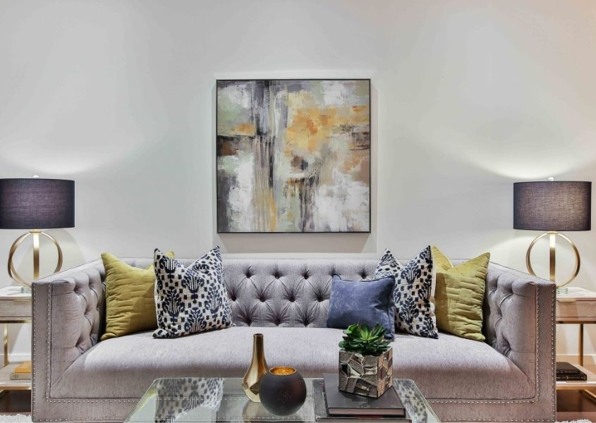 Grey fabric chesterfield sofa with large artwork on the wall and two table lamps