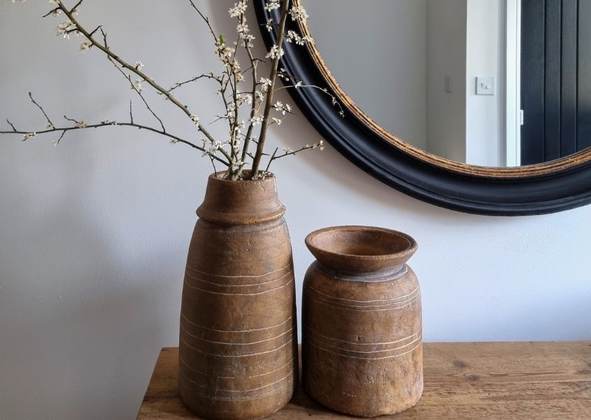 Terracotta vases on a rustic wooden sideboard with a black round mirror