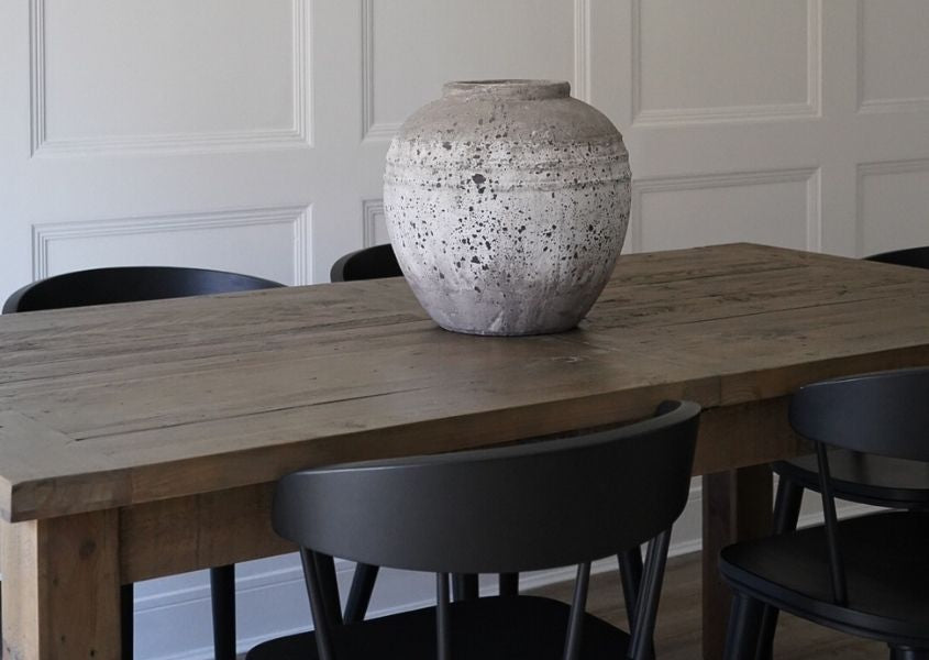 Reclaimed wood table with white stone vase and black dining chairs