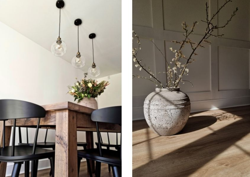 Rustic dining table with three hanging pendant lights, black wood dining chairs and white stone vase