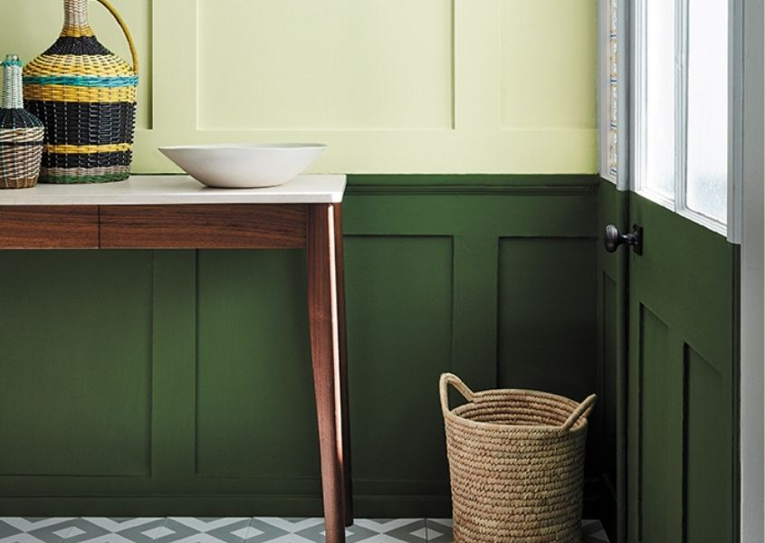 Hallway with dark green painted wood panelling and wooden console table