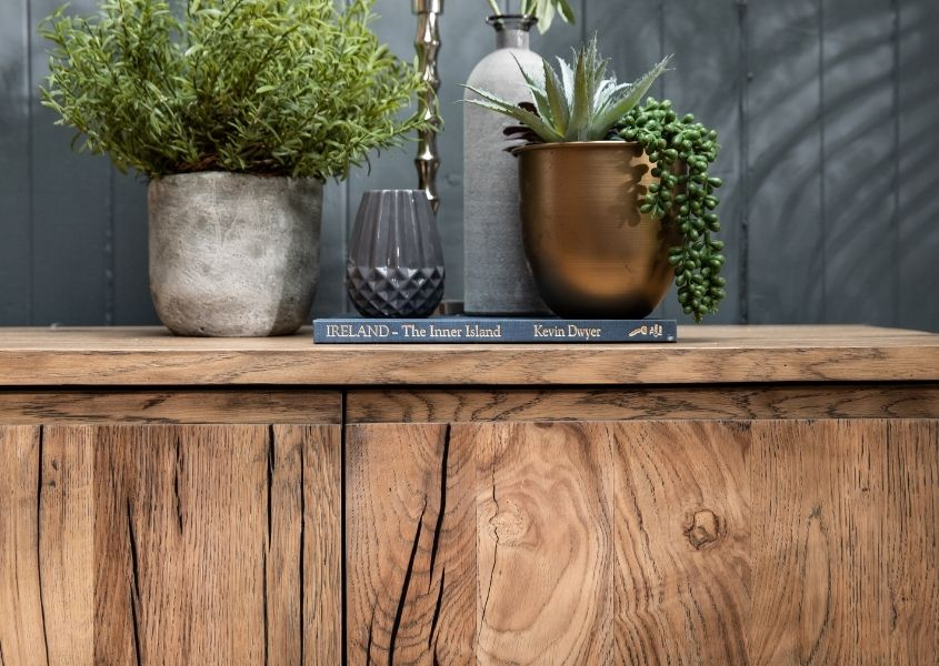 Close up of reclaimed wood furniture with green plants on top