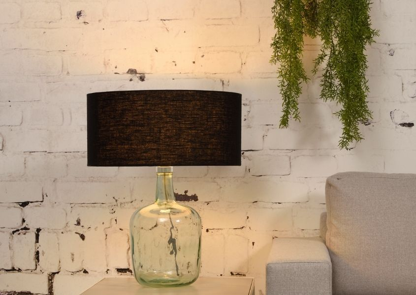 Recycled glass table lamp with dark shade against white brick wall with hanging green plant