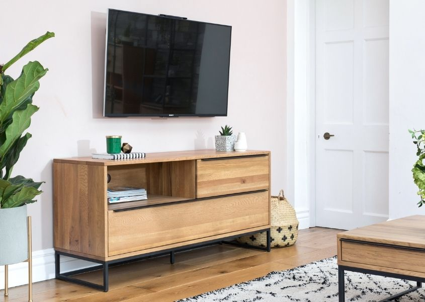 industrial tv unit with tv on wall above and white rug on floor