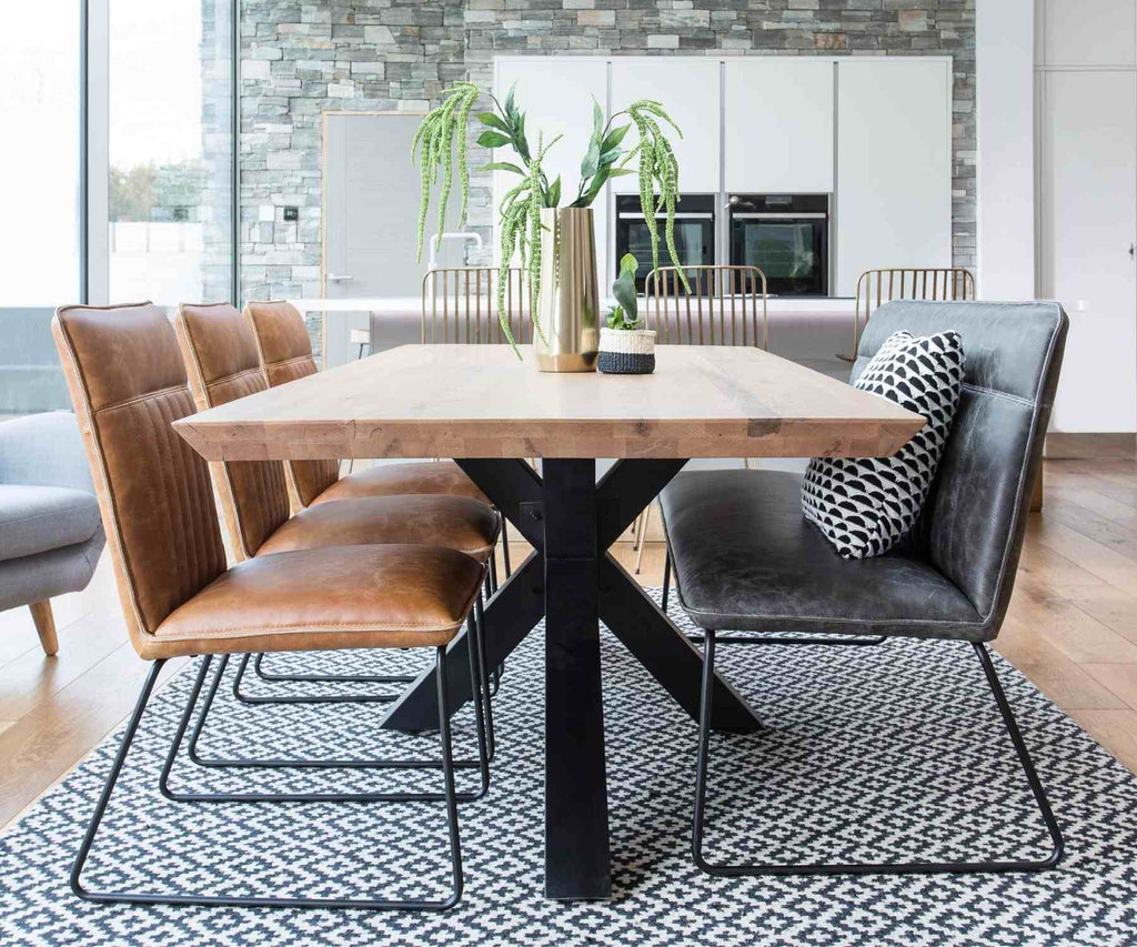 Industrial dining table with black spider legs and faux leather bench and chairs
