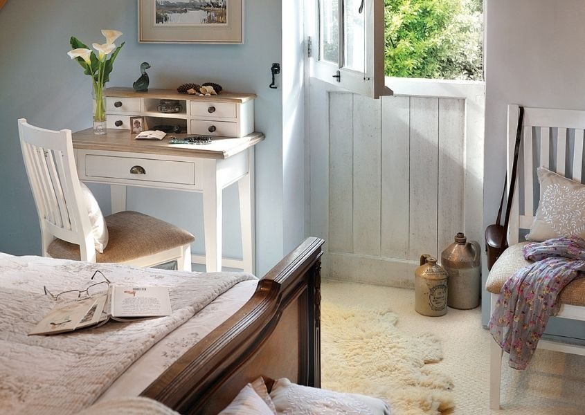 Bedroom with white painted writing desk next to a dark wooden bed and a barn style white painted door