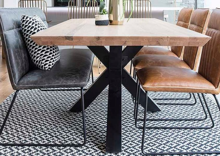 Wooden table with black steel spider legs and grey faux leather bench