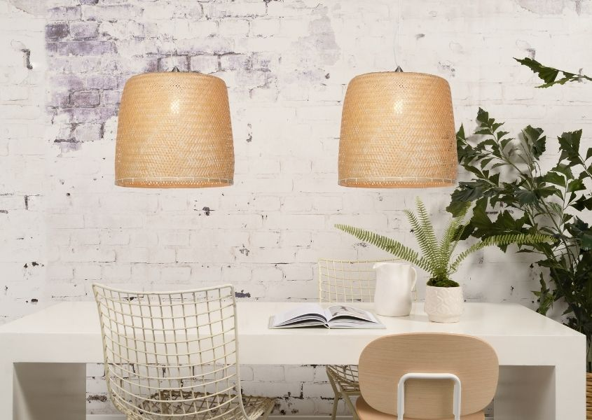 Large bamboo double pendant light over white dining table against white exposed brick wall