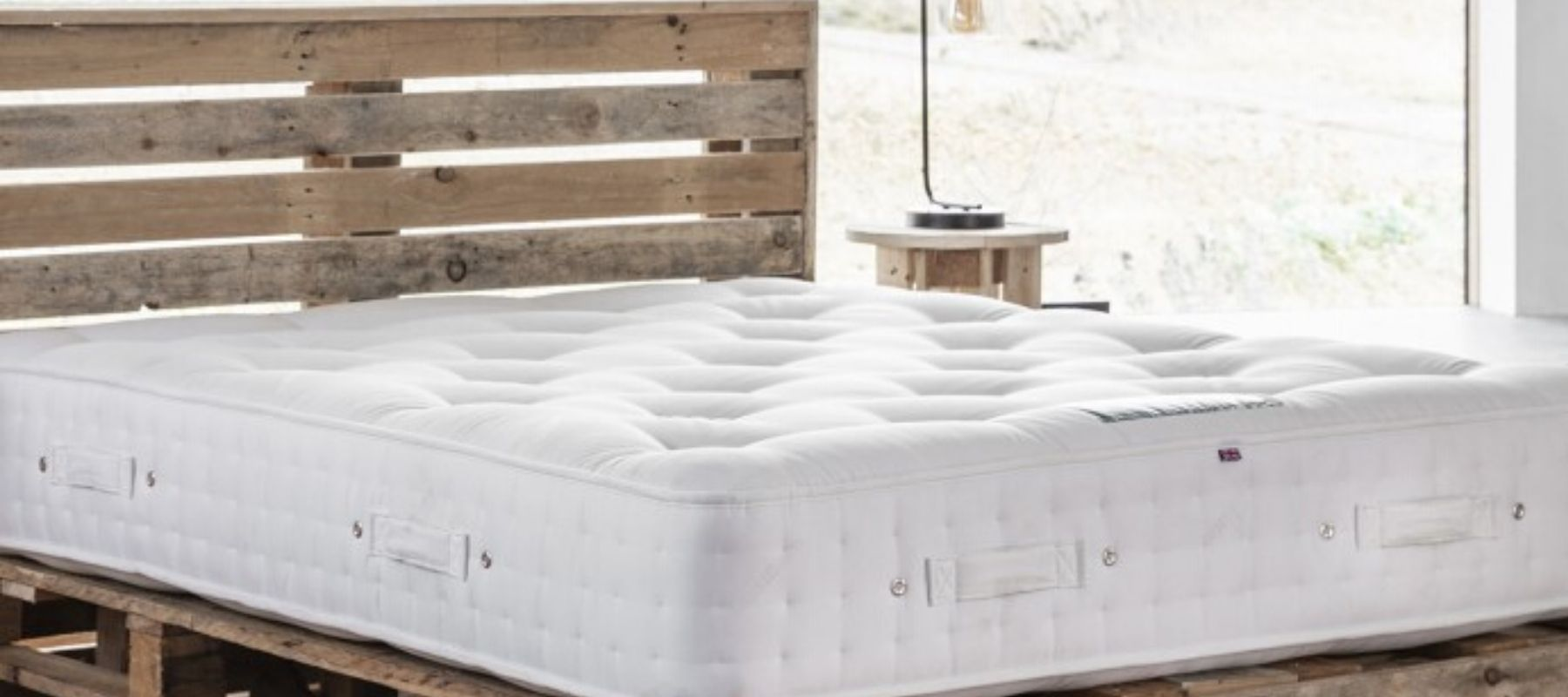 Wooden bed with large white mattress