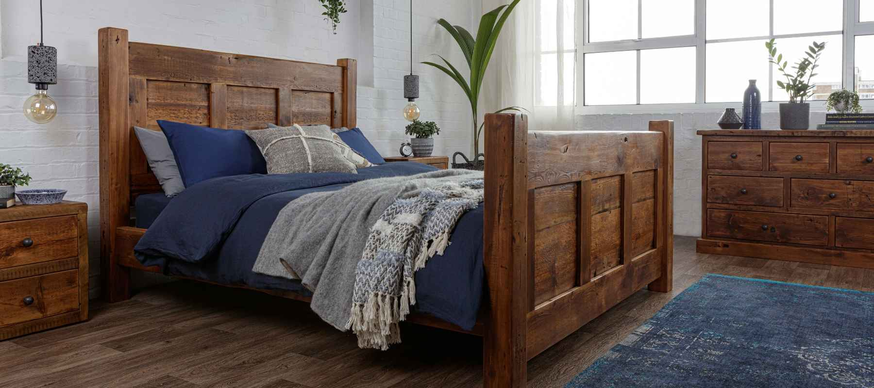 Reclaimed wood bed frame with blue bed covers and blue rug