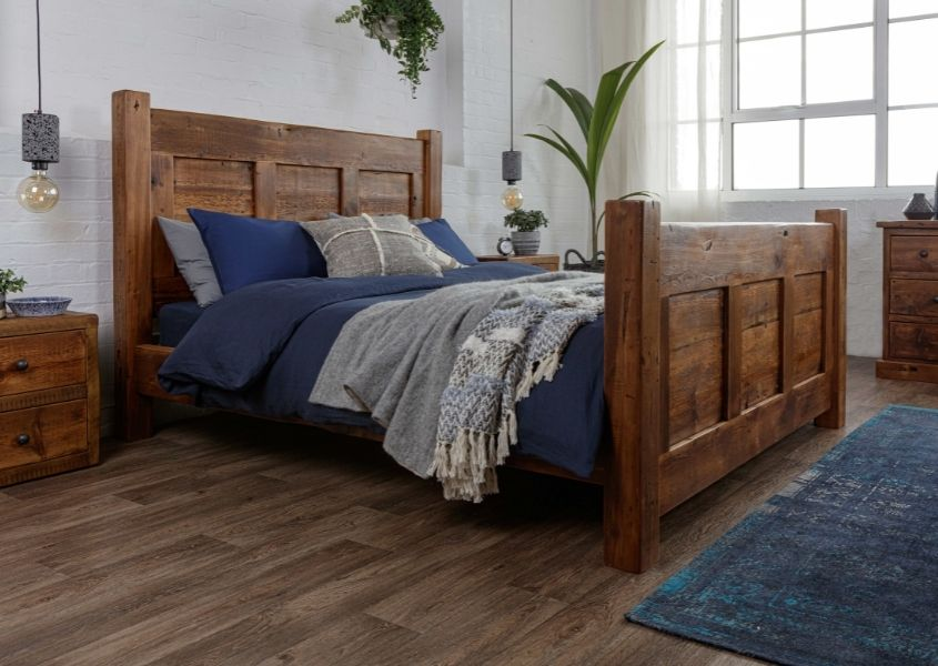 Reclaimed wood bed with high headboard and footboard and dark blue covers