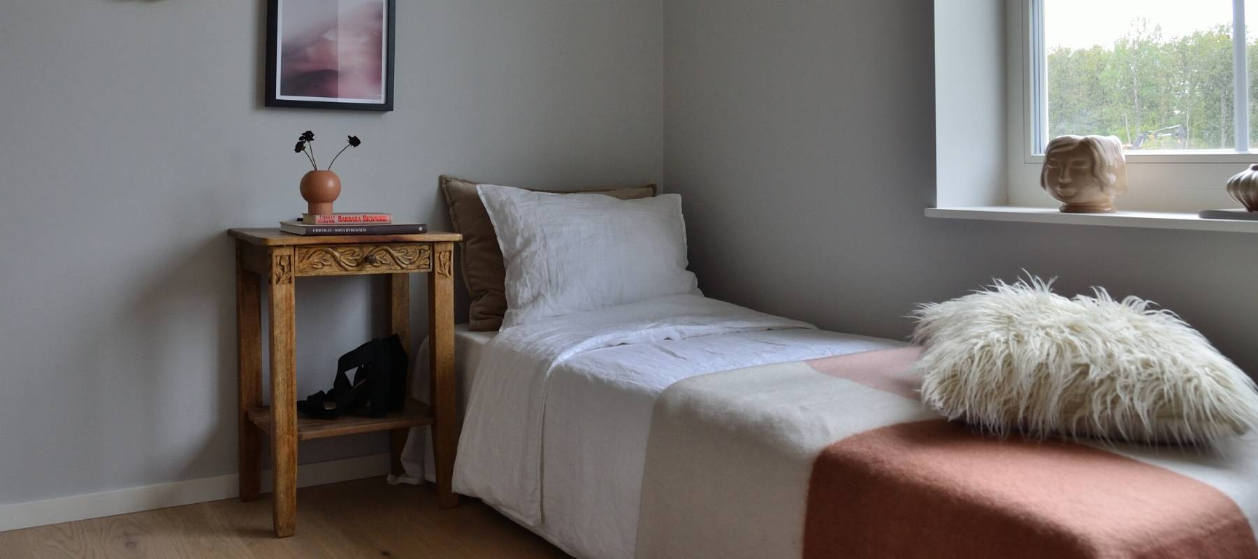 Single bed with sheet and wooden bedside table