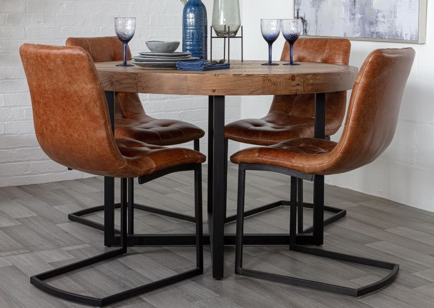 Brown leather dining chairs on black metal u-shaped frame with round dining table
