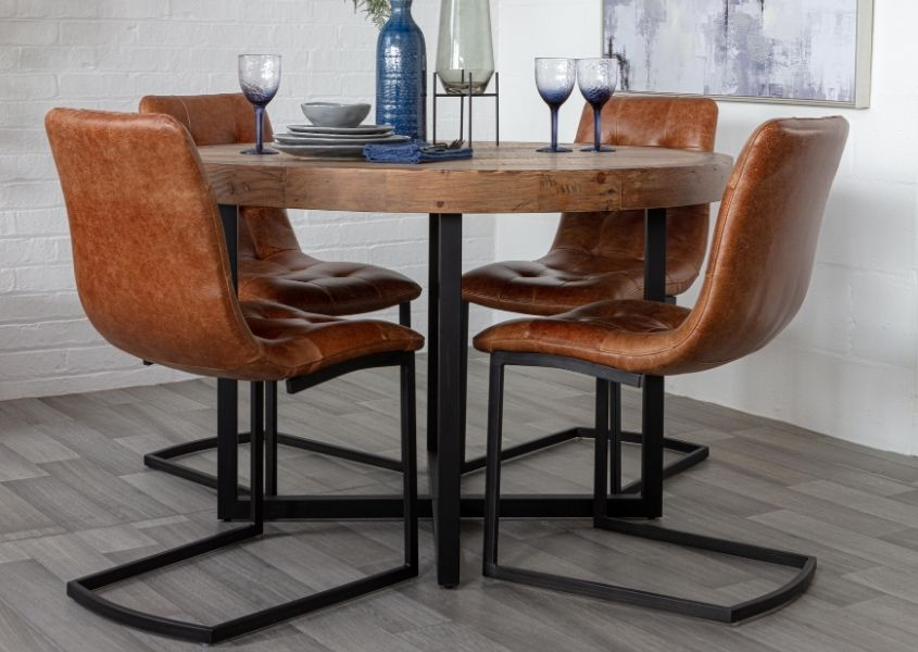 Brown leather dining chairs around a round reclaimed wood dining table