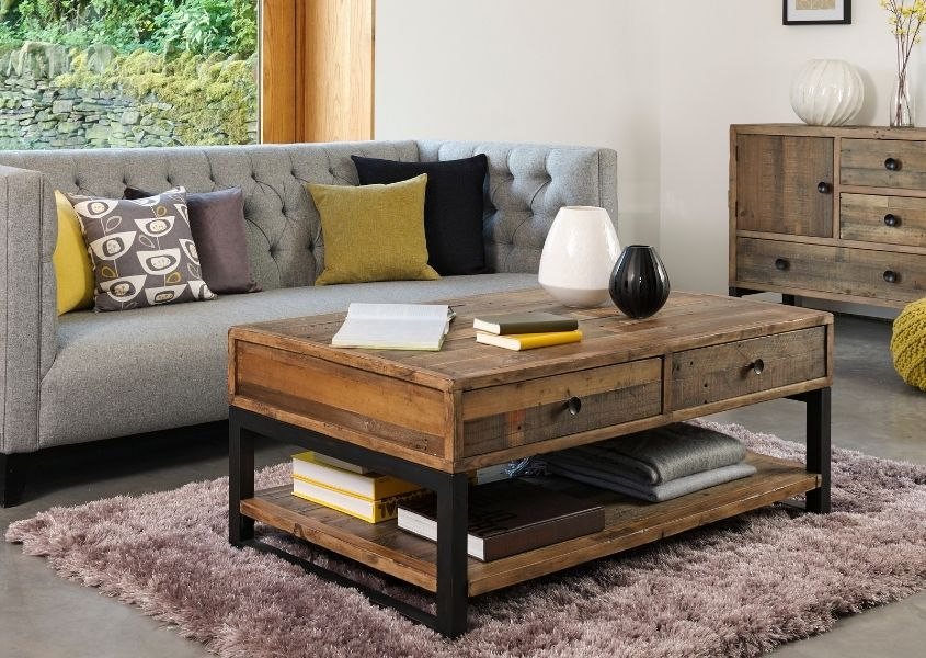 Industrial reclaimed wood coffee table with two drawers in front of a grey sofa