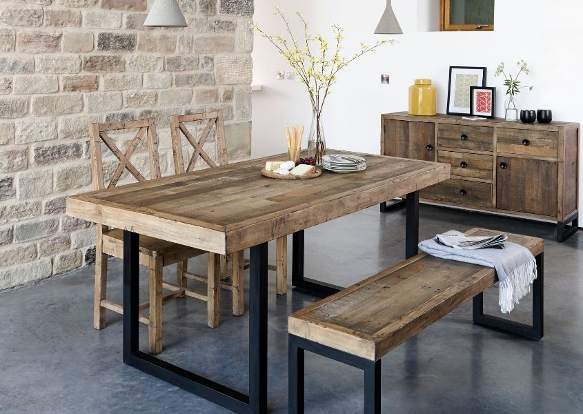 Industrial dining table with matching reclaimed wooden bench in dining room with exposed brick wall