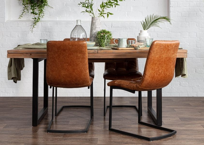 Industrial reclaimed wood dining table with four tan leather industrial dining chairs