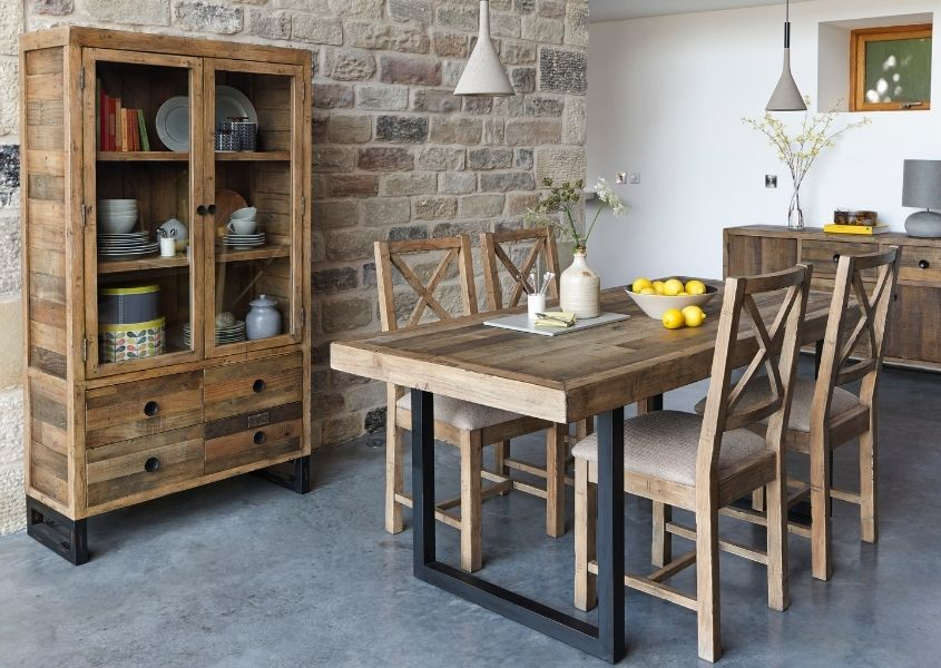 Dining room with reclaimed wood industrial dining table, wooden chairs and rustic glass display cabinet