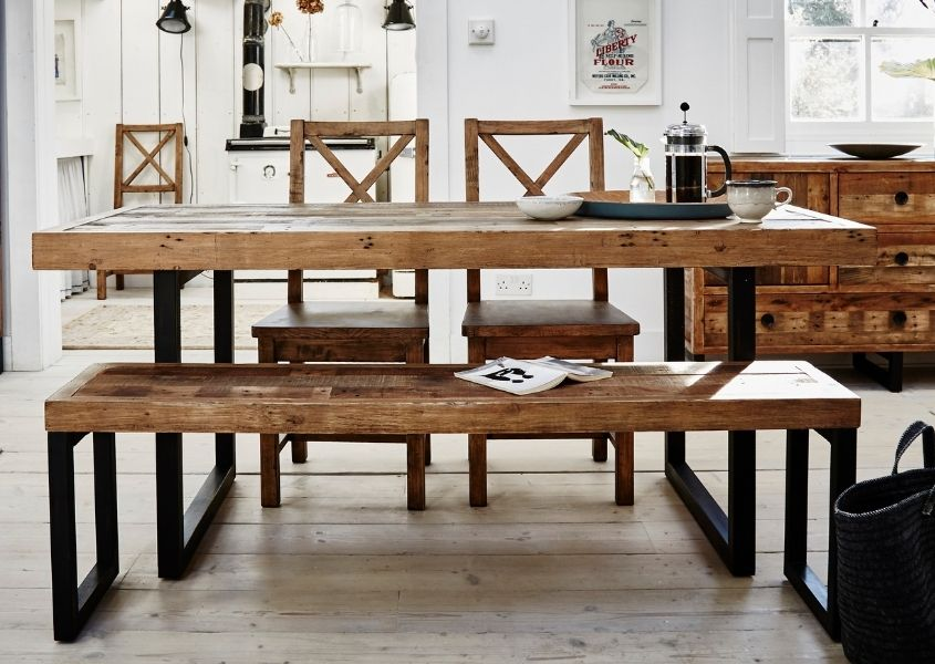 Industrial dining table with black steel legs and matching wooden dining bench in a bright white room