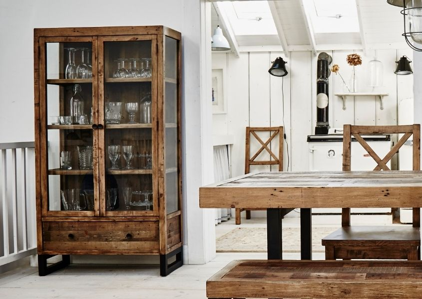 Reclaimed wood glass cabinet in dining room with rustic dining table