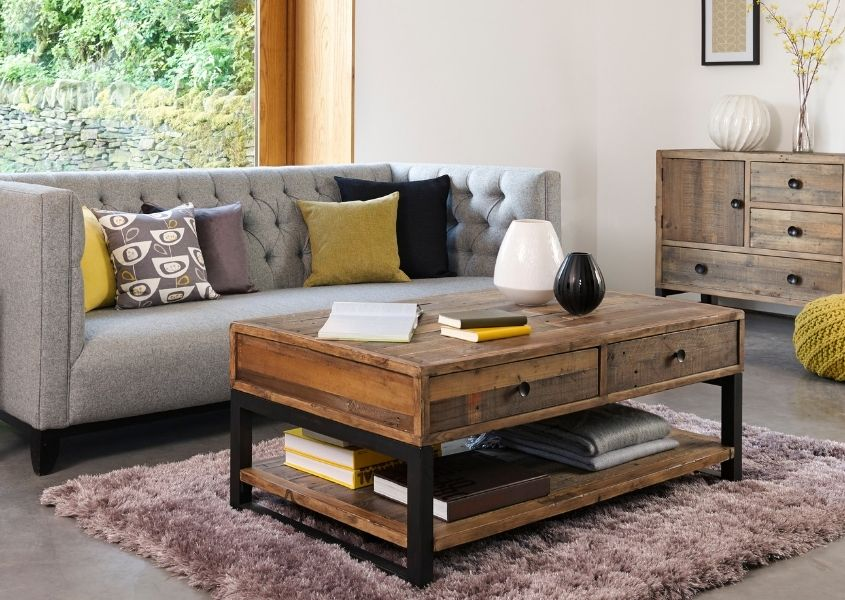 Reclaimed wood coffee table on grey rug with large grey sofa and yellow and grey cushions