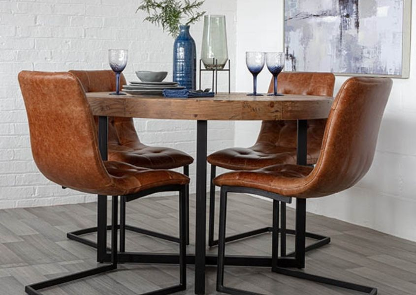 Round industrial dining table with four brown leather dining chairs