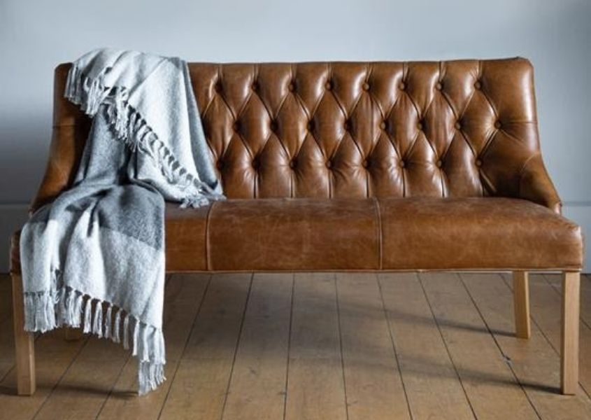 Brown leather dining bench with buttoned back and pale grey throw draped over seat
