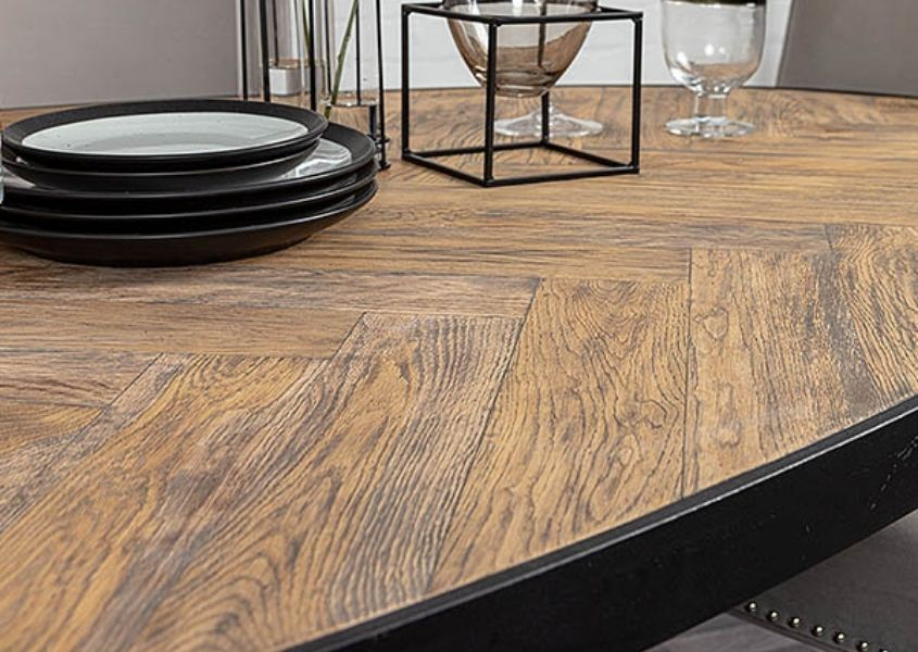 Close up of parquet dining table with black steel frame and small plate on table
