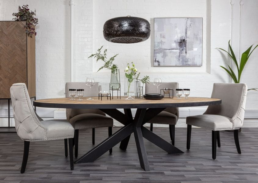 Oval industrial oak dining table with black spider leg and grey velvet dining chairs