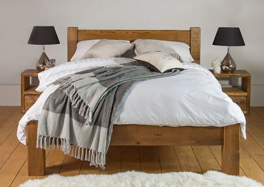 Reclaimed wood bed with white covers and grey blanket thrown on bed with two matching wooden side tables
