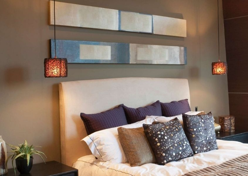 Beige bedroom with padded headboard and two small orange fabric pendant lights beside bed