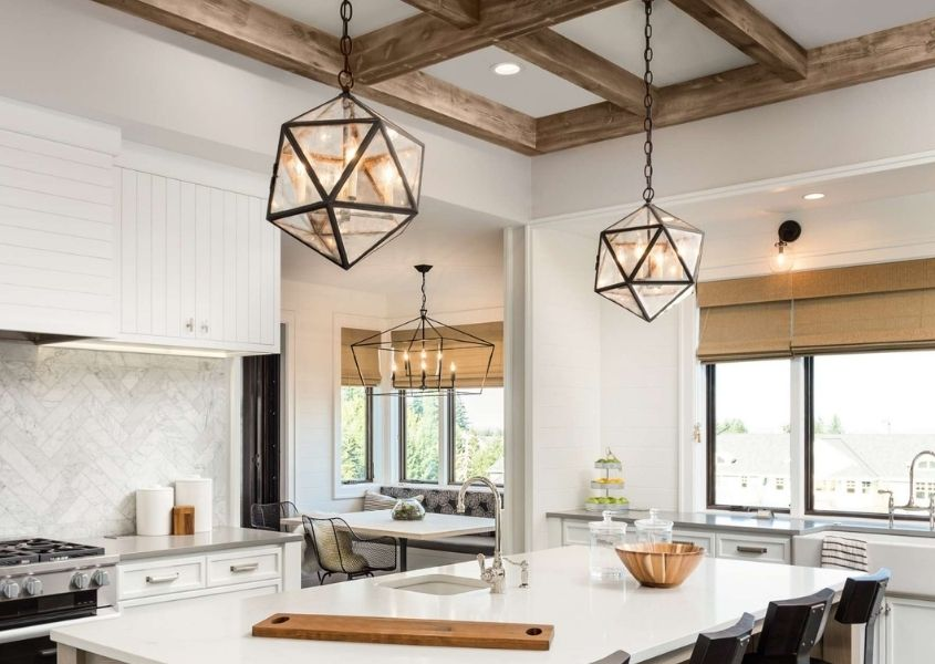 Rustic kitchen with two metal framed hanging pendant lights over breakfast island