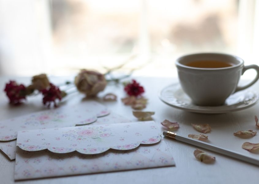 floral note pad and cup of tea on a white writing desk