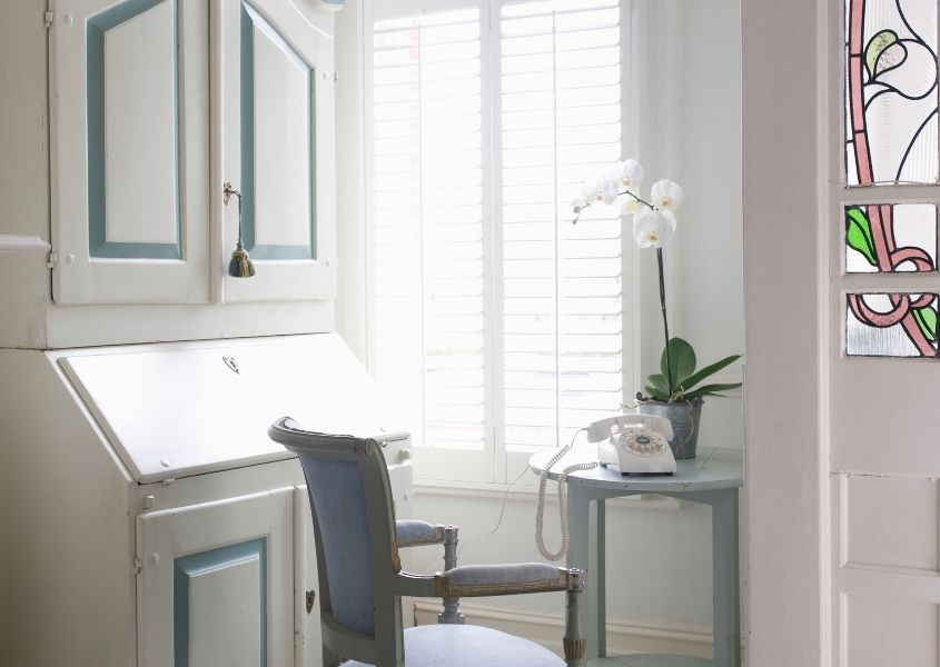 white and blue writing bureau with blue dining chair
