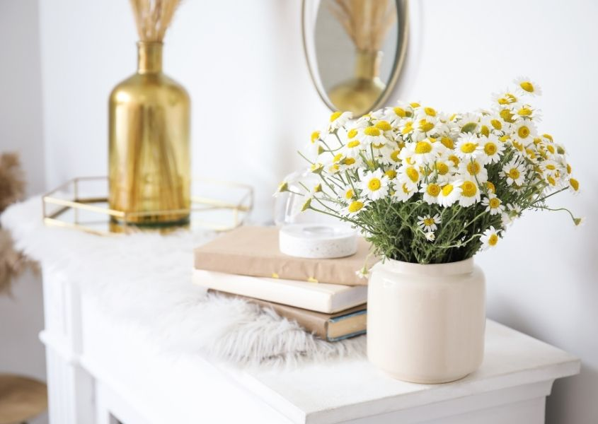 White and yellow flowers in white vase on a fireplace with gold vase and books