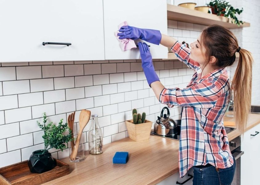 Woman wearing a checked shirt and purple rubber gloves cleaning white kitchen units