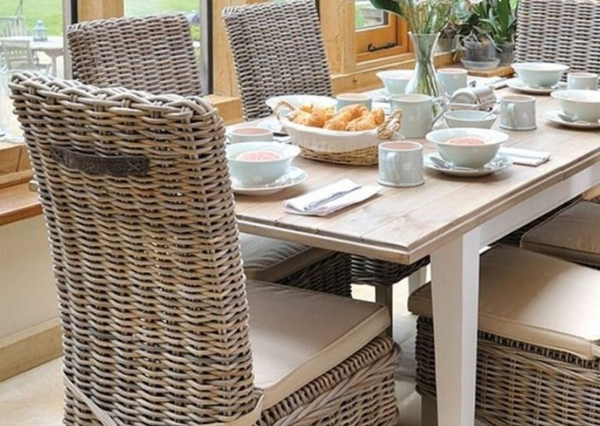 Wooden dining table with white painted legs and high back rattan dining chair