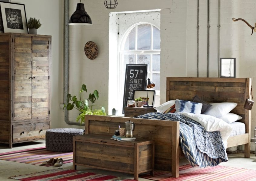 Bedroom with large wooden bed, matching blanket box and double wardrobe and red rug on floor