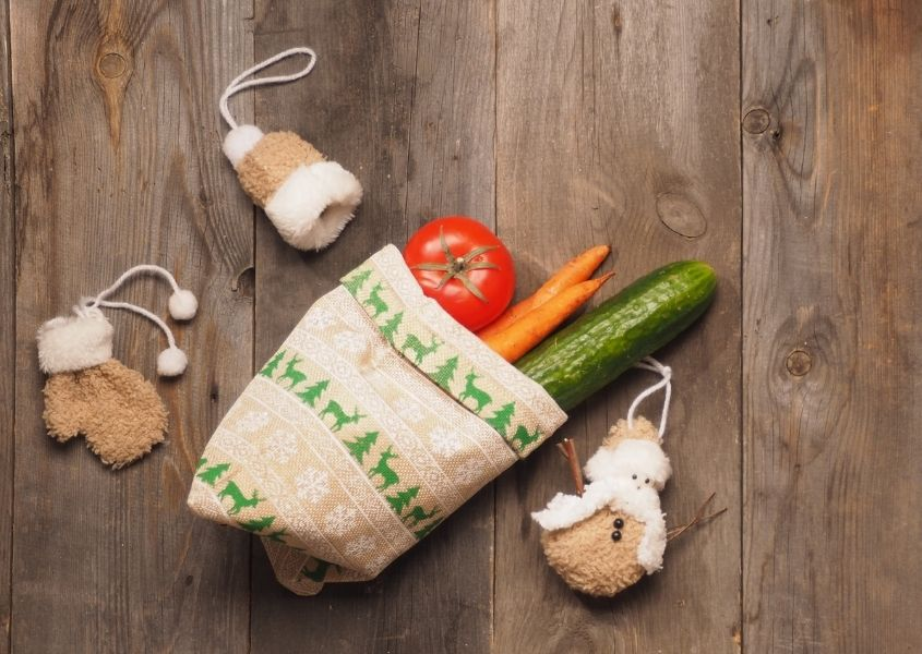 Cucumber, carrot and tomato in small sack on rustic wooden table with fabric Christmas decorations