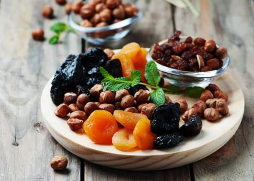 Plate of dried fruits and nuts on rustic wood background