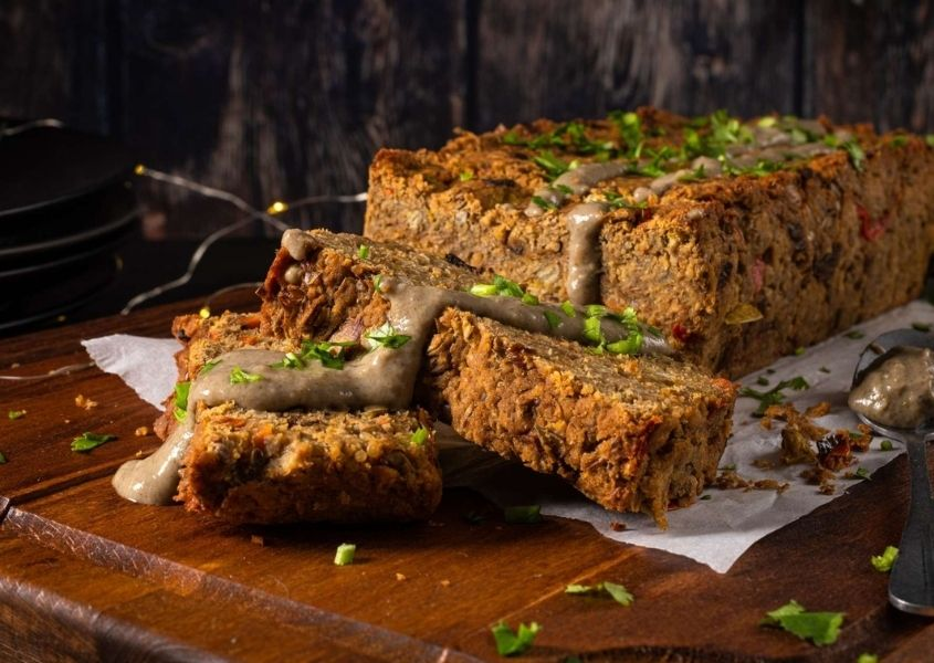 A prepared nut roast with slices cut on brown wooden table