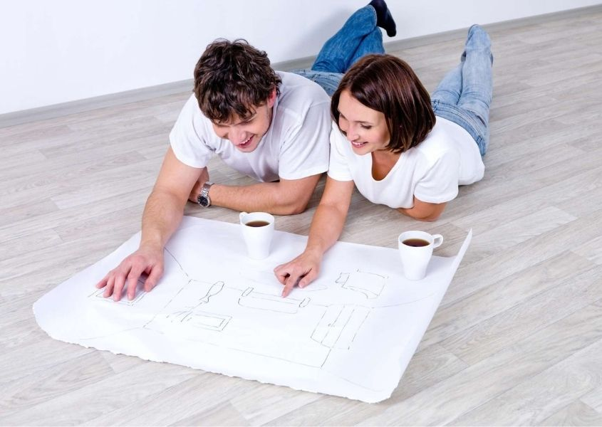 man and woman lying on the floor reading plans for tips for planning the living room and bedroom in your new home blog